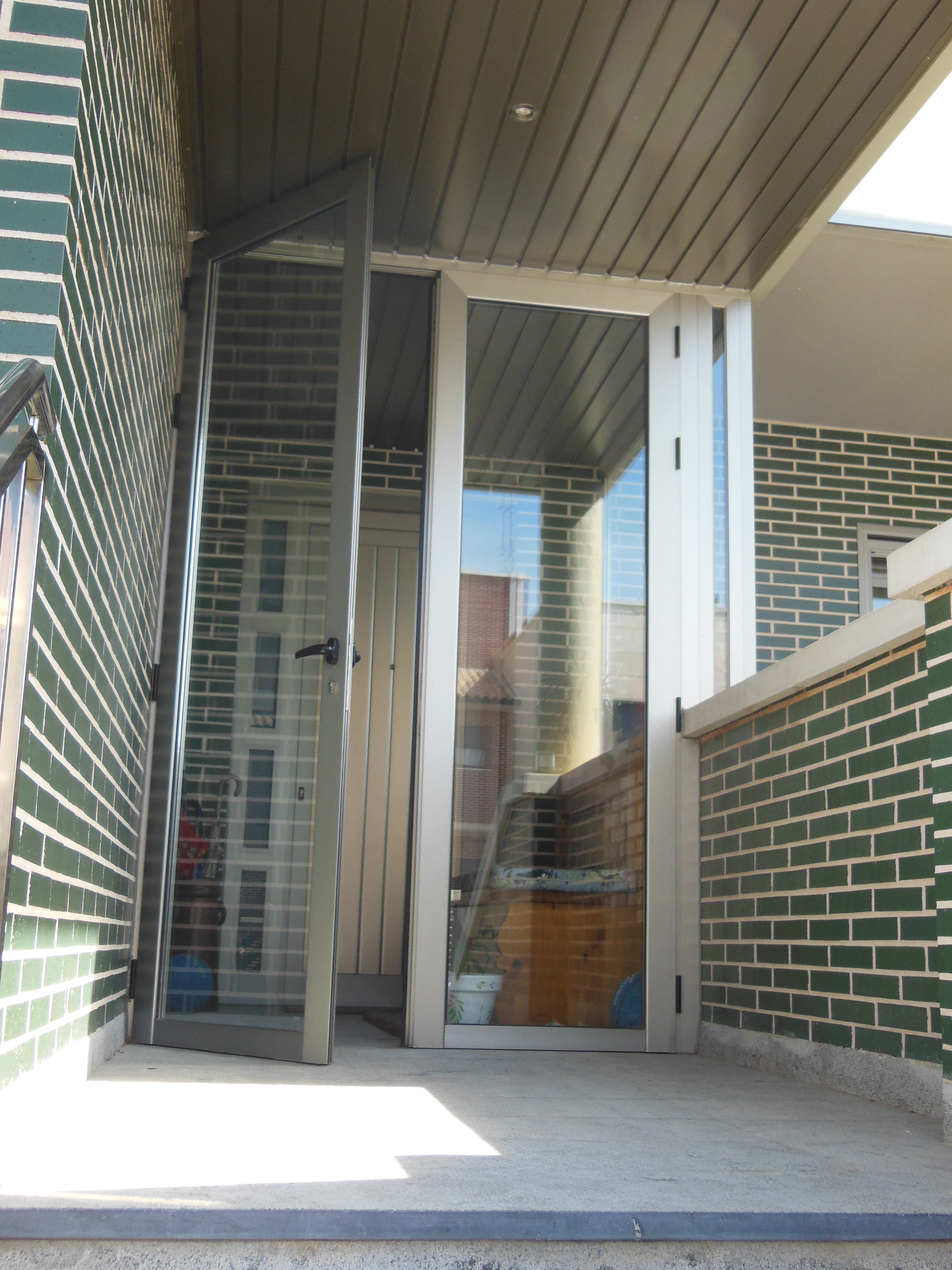 Cerramiento de aluminio en la puerta de entrada montajes for Cerramiento vidrio
